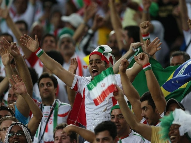 Iran's fans cheer during a Group F football match between Iran and Nigeria at the Baixada Arena in Curitiba at the 2014 FIFA World Cup on June 16, 2014