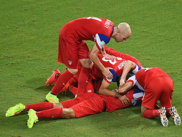 John Brooks of the United States (C) celebrates scoring his team's second goal with Graham Zusi (L) and Fabian Johnson (R) during the 2014 FIFA World Cup match on June 17, 2014