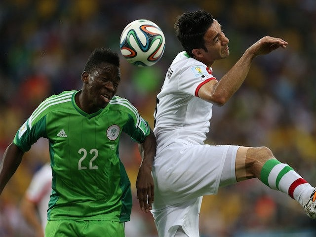 Nigeria's defender Kenneth Omeruo (L) fights for the ball with Iran's midfielder and captain Javad Nekounam during a Group F football match