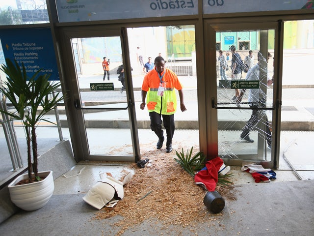 Security personnel stand near broken doors and planters after fans broke through security entering the stadium prior to the 2014 FIFA World Cup Brazil Group B match between Spain and Chile at Maracana on June 18, 2014