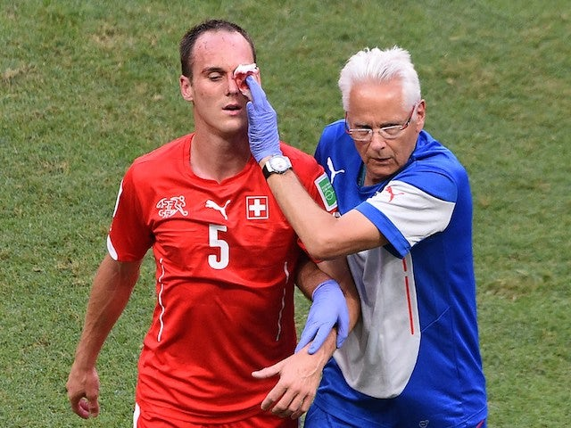 Switzerland's defender Steve von Bergen (L) receives medical assistance after being injured during a Group E football match against France on June 20, 2014