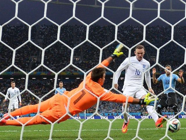 England's forward Wayne Rooney (L) scores against Uruguay's goalkeeper Fernando Muslera (L) during a Group D football match on June 19, 2014