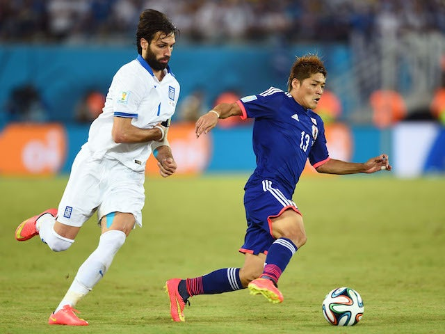 Yoshito Okubo of Japan controls the ball against Giorgos Samaras of Greece during the 2014 FIFA World Cup Brazil Group C match on June 19, 2014