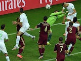 Algeria's forward Islam Slimani heads the ball to score a goal past Russia's goalkeeper Igor Akinfeev during the Group H football match between Algeria and Russia at The Baixada Arena in Curitiba on June 26, 2014
