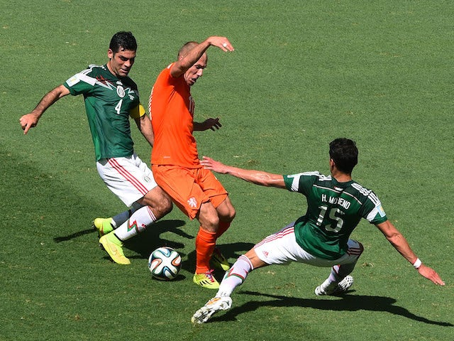 Netherlands winger Arjen Robben is tackled by Mexico duo Hector Moreno and Rafael Marquez during the World Cup last-16 tie in Fortaleza on June 29, 2014