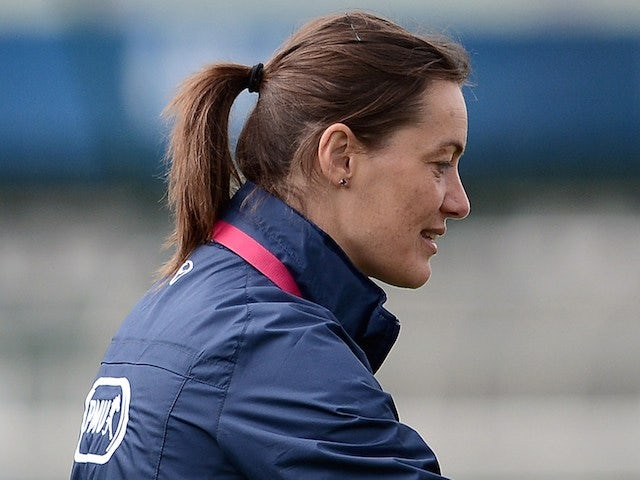 French women's national football team assistant coach Corinne Diacre (L) gives instructions to midfielder Camille Catala during a training session on June 25, 2013