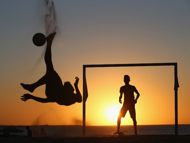 Locals play football at the Iracemar beach on June 22, 2014 in Fortaleza, Brazil