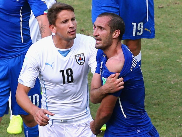 Giorgio Chiellini of Italy pulls down his shirt after a clash with Luis Suarez of Uruguay (not pictured) as Gaston Ramirez of Uruguay looks on June 24, 2014