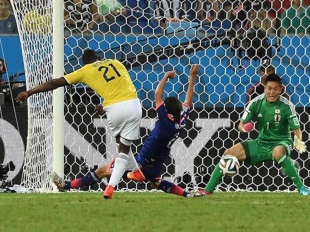Colombia's forward Jackson Martinez (L) strikes to score a goal as Japan's goalkeeper Eiji Kawashima defends during the Group C football match on June 24, 2014
