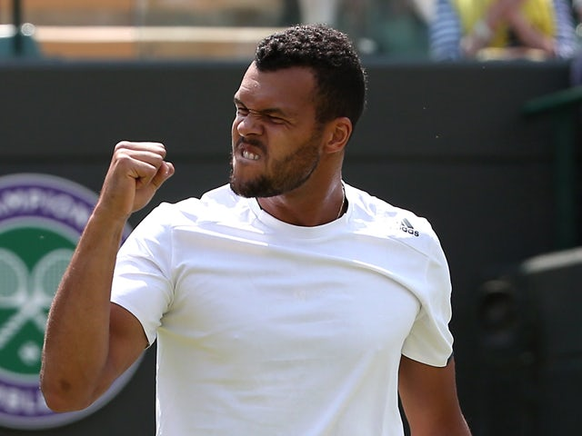 France's Jo-Wilfried Tsonga celebrates match point during his men's singles first round match against Austria's Jurgen Melzer, a day after the game was suspended due to rain, on day two of the 2014 Wimbledon Championships at The All England Tennis Club in
