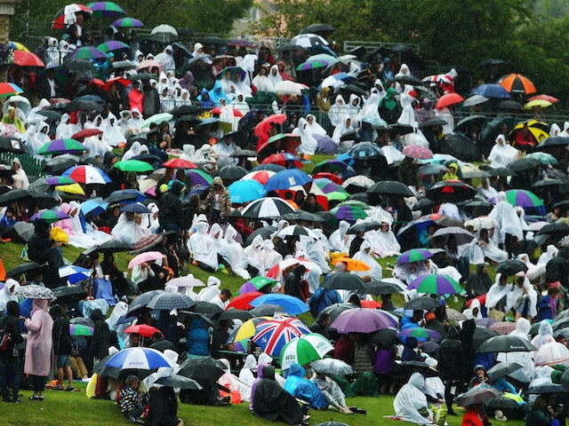 Fans sitting on Murray mound shelter under umbrellas as rain delays the start of play on day six of the Wimbledon Lawn Tennis Championships on June 28, 2014