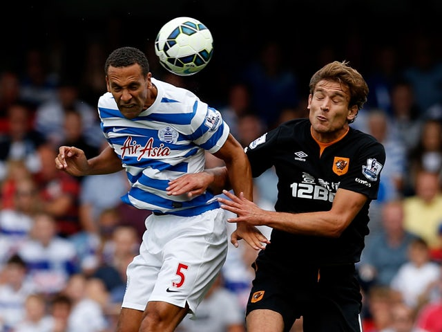 Rio Ferdinand of QPR and Nikica Jelevic of Hull City during the Barclays Premier League match between Queens Park Rangers and Hull City at Loftus Road on August 16, 2014