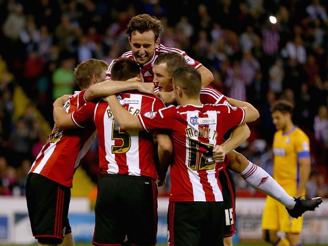 Andy Butler of Sheffield United celebrates with his team mates after scoring his teams first goal during the Capital One Cup First Round match between Sheffield United and Mansfield Town at Bramell Lane on August 13, 2014