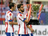 Atletico Madrid's midfielder Raul Garcia carries the 2013-2014 Spanish Liga Champions trophy before the Spanish league football match Club Atletico de Madrid vs S.D Eibar at the Vicente Calderon stadium in Madrid on August 30, 2014