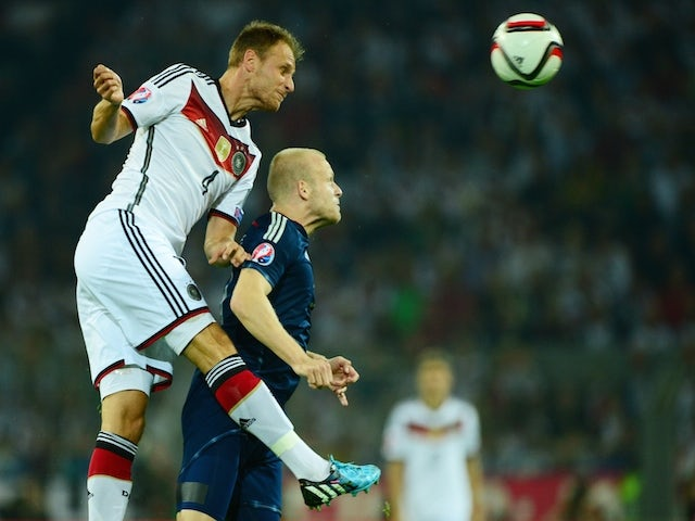Germany's defender Benedikt Hoewedes (L) and Scotland's forward Steven Naismith vie for the ball during the UEFA Euro 2016 Group D qualifying match of Germany vs Scotland on September 7, 2014