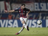 Argentina's San Lorenzo midfielder Ignacio Piatti strikes to scoring the team's third goal against Brazil's Botafogo during the Copa Libertadores 2014 group 2 football match at Pedro Bidegain stadium in Buenos Aires, Argentina, on April 9, 2014