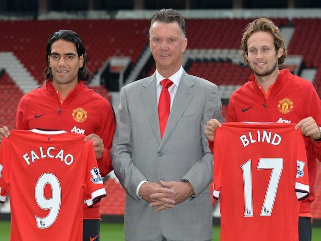 Manchester United's Dutch manager Louis van Gaal (C) poses for photographs along with the club's latest signings Colombian striker Radamel Falcao (L) and Dutch midfielder Daley Blind on September 11, 2014