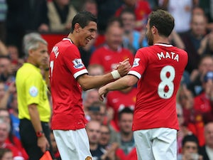 Angel Di Maria of Manchester United is congratulated by team-mate Juan Mata after scoring the first goal during the Barclays Premier League match between Manchester United and Queens Park Rangers at Old Trafford on September 14, 2014
