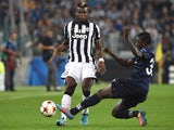 Paul Pogba (L) of Juventus is tackled by Pa Konate of Malmo FF during the UEFA Champions League Group A match between Juventus and Malmo FF on September 16, 2014