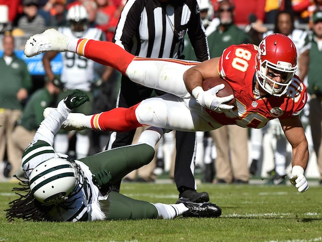 Anthony Fasano #80 of the Kansas City Chiefs dives over Marcus Williams #22 of the New York Jets during the first half at Arrowhead Stadium on November 2, 2014