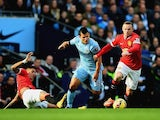Marcos Rojo of Manchester United slides in as Sergio Aguero of Manchester City and Wayne Rooney battle for the ball during the Barclays Premier League game at the Etihad on November 2, 2014