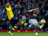 Aaron Cresswell of West Ham passes the ball under pressure from Alex Oxlade-Chamberlain of Arsenal during the Barclays Premier League match on December 28, 2014
