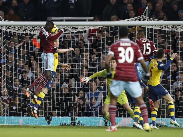 West Ham United's Senegalese midfielder Cheikhou Kouyate (L) scores their first goal during the English Premier League football match against Arsenal on December 28, 2014