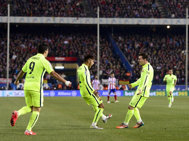 Barcelona's Brazilian forward Neymar celebrates with Barcelona's Argentinian forward Lionel Messi after scoring the equalizer during the Spanish Copa del Rey (King's Cup) quarter final second leg football match Club Atletico de Madrid vs FC Barcelona at t