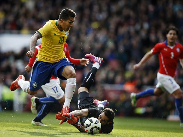 Brazil's midfielder Roberto Firmino (L) takes the ball past Chile's goalkeeper Claudio Bravo (2nd R) to score the only goal of the friendly international football match between Brazil and Chile at The Emirates Stadium in London on March 29, 2015
