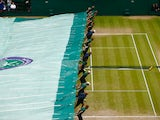 The covers come on during a rain break in the Final Of The Gentlemen's Singles between Novak Djokovic of Serbia and Roger Federer of Switzerland on day thirteen of the Wimbledon Lawn Tennis Championships at the All England Lawn Tennis and Croquet Club on