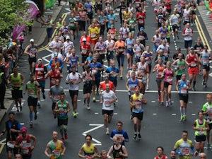 Runners make their way through Canary Wharf during the Virgin Money London Marathon on April 26, 2015