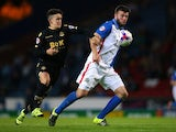 Grant Hanley of Blackburn Rovers holds off a challenge from Zach Clough of Bolton Wanderers during the Sky Bet Championship match between Blackburn Rovers and Bolton Wanderers at Ewood park on August 28, 2015