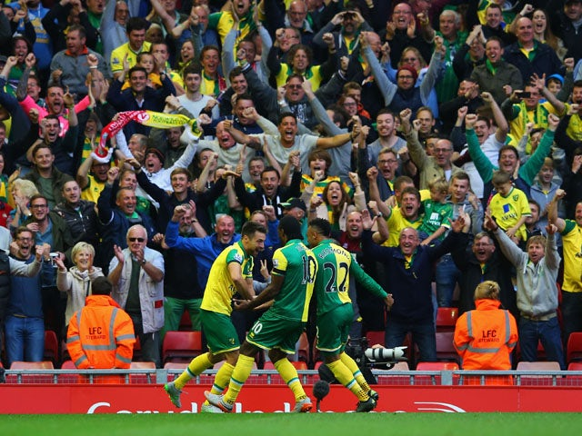 Russell Martin of Norwich City (L) celebrates in front of the travelling fans with team mates as he scores their first and equalising goal during the Barclays Premier League match between Liverpool and Norwich City at Anfield on September 20, 2015