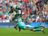 Brandon Marshall of the New York Jets is tackled by Brent Grimes of the Miami Dolphins on October 4, 2015
