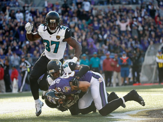 Crockett Gillmore #80 of the Baltimore Ravens catches a first half touchdown pass in front of Johnathan Cyprien #37 and Thurston Armbrister #57 of the Jacksonville Jaguars at M&T Bank Stadium on November 15, 2015