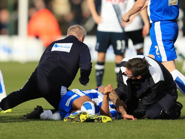 Alex Wynter of Colchester United receives the medical treatment before being stretched off during the FA Cup fourth-round match against Tottenham Hotspur on January 30, 2016