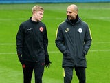 Kevin De Bruyne shares a joke with Pep Guardiola during a Manchester City training session on November 22, 2016