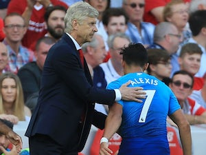Arsene Wenger pats Alexis Sanchez on the back during the Premier League game between Liverpool and Arsenal on August 27, 2017