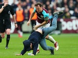 Mark Noble destroys a pitch invader during the Premier League game between West Ham United and Burnley on March 10, 2018
