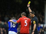 Phil Neville hangs his head in shame as he is booked for simulation