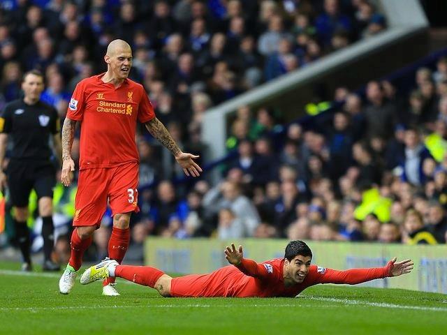 Luis Suarez dives to the ground to celebrate