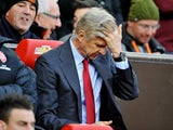 Arsene Wenger runs his fingers through his hair in frustration