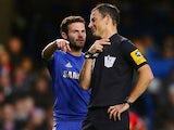 Mark Clattenburg argues with Juan Mata