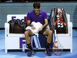 Roger Federer sits with his head down