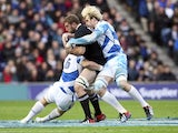 Luke Romano is tackled by Scotland's Alasdair Strokosch
