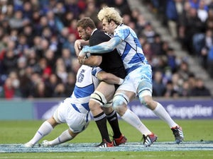 Luke Romano is tackled by Scotland's Alasdair Strokosch