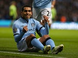 Carlos Tevez celebrating from the ground after scoring on November 17, 2012