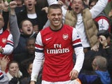 Lukas Podolski smiles after scoring Arsenal's second on November 17, 2012