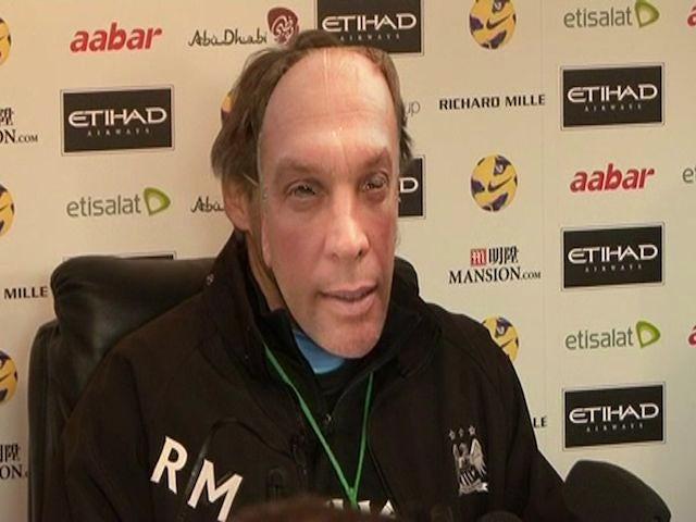 Roberto Mancini wears a David Platt mask at his press conference on November 16, 2012