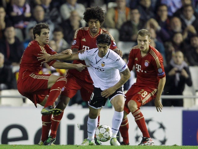 Valencia's Ever Banega challenges three Bayern players on November 20, 2012